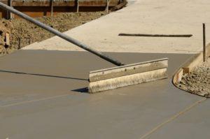 Worker resurfacing newly installed concrete sidewalk
