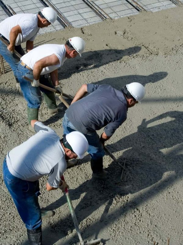 Four workers are paving concrete to construct concrete surface for commercial building